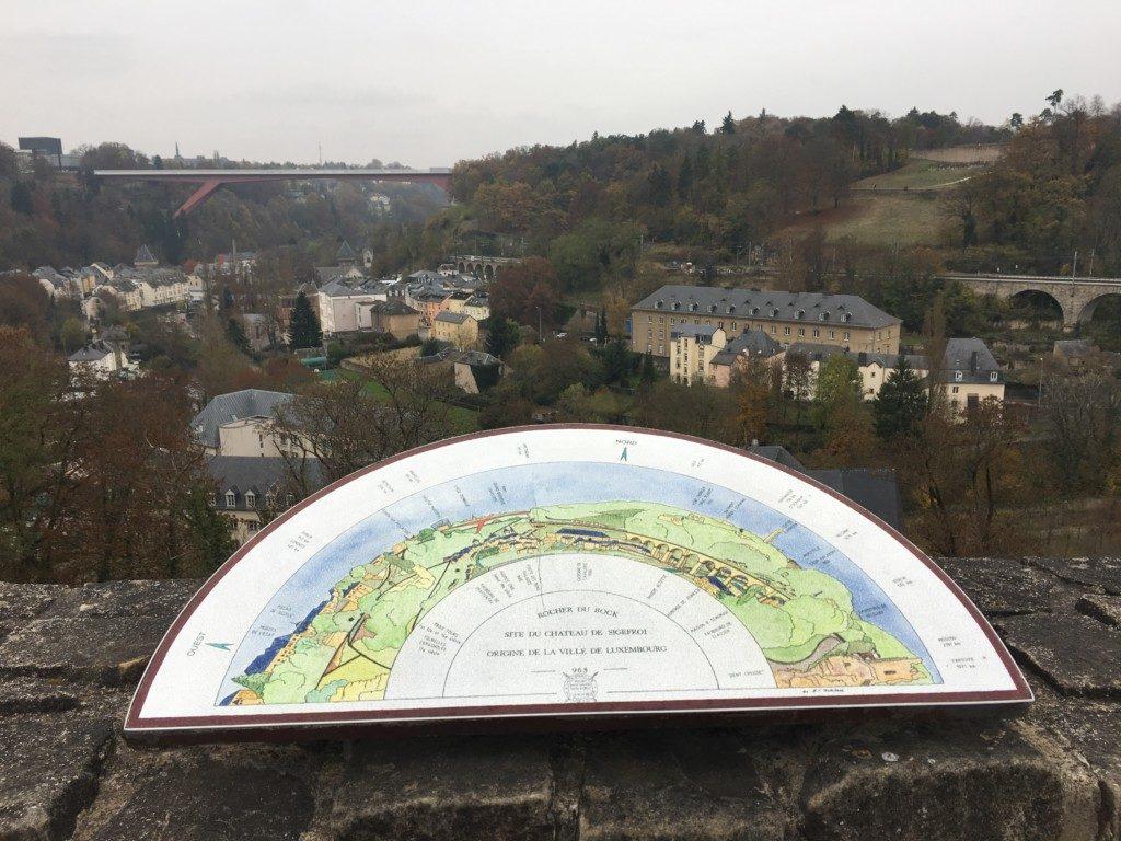 W oddali widać most Pont Grand-Duchesse Charlotte, zwany też Czerwonym Mostem. Łączący dawną Twierdzę Luksemburg z nowoczesną dzielnicą Kirchberg. Most oddano do użytku w 1965 roku. Wykonany ze stali posiada 74 m wysokości (przerzucony jest nad dzielnicą Pfaffenthal), 25,07 m szerokości, a jego łączna długość wynosi 355 m.